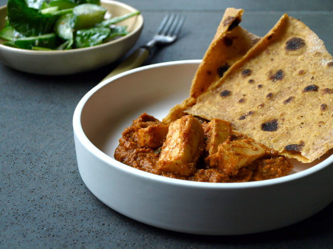 Indian paneer cheese in spiced tomato sauce with cardamom sweet potato roti