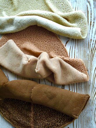 Injera in three colours - wheat (white), sorghum (pink) and teff (brown)